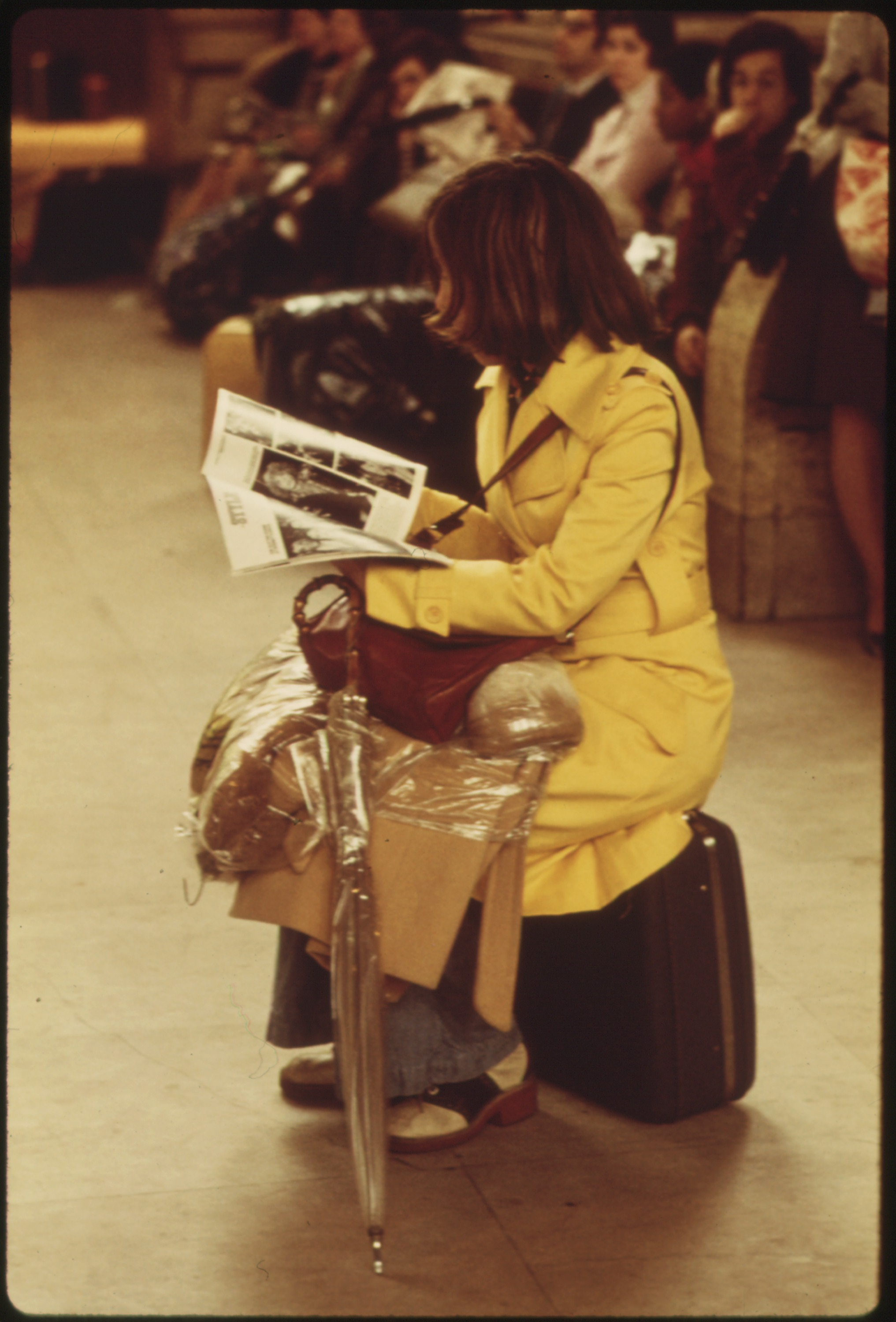 PASSENGER_PERCHES_ON_HER_SUITCASE_WHILE_WAITING_FOR_A_TRAIN_AT_THE_30TH_STREET_STATION_IN_PHILADELPHIA,_PENNSYLVANIA...._-_NARA_-_556699